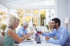 Groupe d'amis grillant des verres de vin pendant le repas Images libres de droits