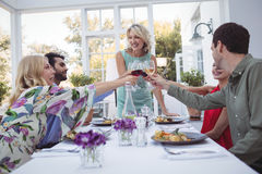 Groupe d'amis grillant des verres de vin pendant le repas Photos libres de droits