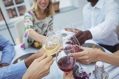 Groupe d'amis grillant des verres de vin pendant le repas Photos stock