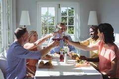 Groupe d'amis grillant des verres de vin rouge Image stock