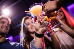 Groupe d'amis grillant le cocktail au compteur de barre Image libre de droits