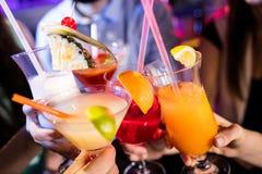 Groupe d'amis grillant le cocktail au compteur de barre Photographie stock