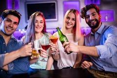Groupe d'amis grillant le cocktail, la bouteille à bière et le verre de bière au compteur de barre Images libres de droits