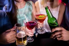 Groupe d'amis grillant le cocktail, la bouteille à bière et le verre de bière au compteur de barre Photos libres de droits
