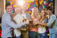 Groupe d'amis grillant le verre de bière Photographie stock