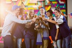 Groupe d'amis grillant le verre de bière en partie Image stock