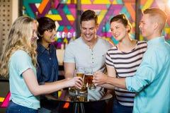 Groupe d'amis grillant le verre de bière en partie Photographie stock
