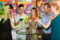 Groupe d'amis grillant le verre du cocktail dans la barre Photo libre de droits