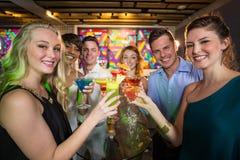 Groupe d'amis grillant le verre du cocktail dans la barre Images stock