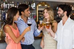 Groupe d'amis grillant le vin rouge et le champagne Photo stock