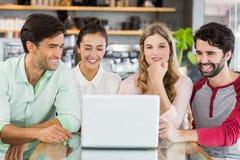 Groupe d'amis heureux à l'aide de l'ordinateur portable Photographie stock