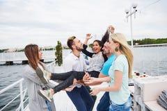 Groupe d'amis heureux à la plage, homme jetant une femme en l'air heureuse Photographie stock