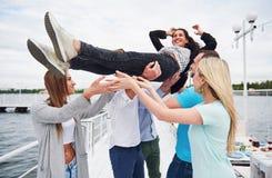 Groupe d'amis heureux à la plage, homme jetant une femme en l'air heureuse Images libres de droits