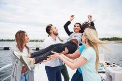 Groupe d'amis heureux à la plage, homme jetant une femme en l'air heureuse Image libre de droits