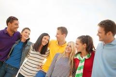 Groupe d'amis heureux étreignant et parlant Image libre de droits
