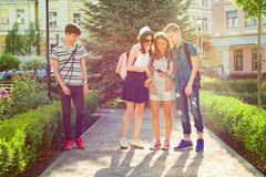 Groupe d'amis heureux 13, 14 ans d'adolescents marchant le long de la rue de ville Image libre de droits