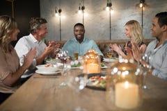 Groupe d'amis heureux applaudissant l'homme tout en dinant Photographie stock
