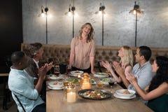 Groupe d'amis heureux applaudissant la femme tout en dinant Photos libres de droits