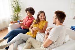 Groupe d'amis heureux avec de la bière parlant à la maison Images stock