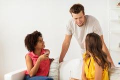 Groupe d'amis heureux avec des boissons parlant à la maison Photographie stock libre de droits