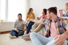Groupe d'amis heureux avec des boissons parlant à la maison Image libre de droits