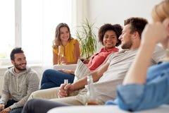 Groupe d'amis heureux avec des boissons parlant à la maison Images libres de droits