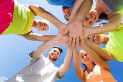 Groupe d'amis heureux avec des mains sur le dessus dehors Photographie stock libre de droits