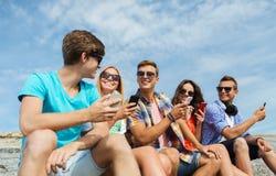 Groupe d'amis heureux avec des smartphones dehors Photographie stock