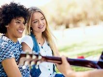 Groupe d'amis heureux avec la guitare ayant l'amusement extérieur Photos libres de droits