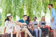 Groupe d'amis heureux avec la guitare Tandis que l'un d'entre eux joue la guitare et d'autres lui donnent une salve d'applaudisse image libre de droits