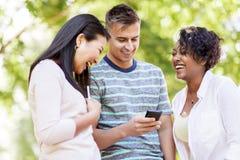 Groupe d'amis heureux avec le smartphone dehors Photos stock