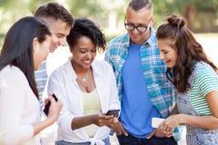 Groupe d'amis heureux avec le smartphone dehors Photo stock