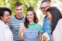 Groupe d'amis heureux avec le smartphone dehors Photo libre de droits