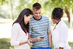 Groupe d'amis heureux avec le smartphone dehors Photographie stock libre de droits