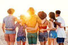 Groupe d'amis heureux ayant l'amusement à la plage d'océan Photo libre de droits