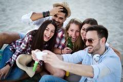 Groupe d'amis heureux ayant l'amusement à la plage en été Images stock