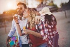 Groupe d'amis heureux ayant l'amusement à la plage en été Photographie stock libre de droits