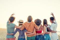 Groupe d'amis heureux ayant l'amusement à la plage d'océan Image libre de droits