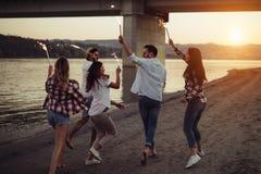 Groupe d'amis heureux ayant l'amusement sur la plage la nuit Photographie stock