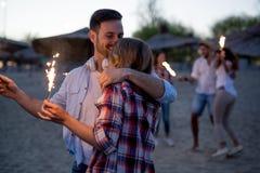 Groupe d'amis heureux ayant l'amusement sur la plage la nuit Images libres de droits