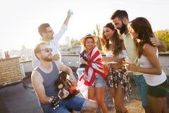 Groupe d'amis heureux ayant la partie sur le dessus de toit Image libre de droits