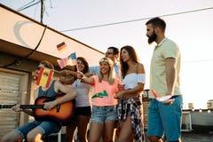 Groupe d'amis heureux ayant la partie sur le dessus de toit Photos stock