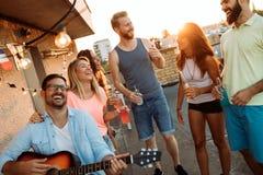 Groupe d'amis heureux ayant la partie sur le dessus de toit Photo stock