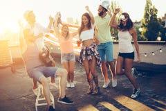 Groupe d'amis heureux ayant la partie sur le dessus de toit Photo libre de droits