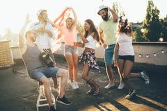 Groupe d'amis heureux ayant la partie sur le dessus de toit photos libres de droits