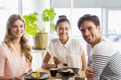 Groupe d'amis heureux ayant le dessert ensemble Photo stock