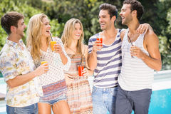 Groupe d'amis heureux ayant le jus près de la piscine Photos stock
