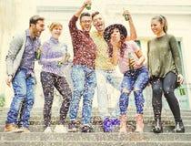 Groupe d'amis heureux ayant les bières potables d'une fête de rue tandis que les confettis tombent vers le bas images stock