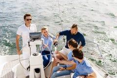 Groupe d'amis heureux ayant une partie sur un yacht Photos stock