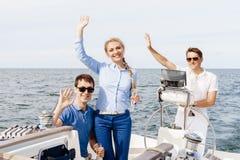 Groupe d'amis heureux ayant une partie sur un yacht et buvant le ch Images libres de droits
